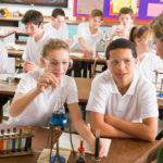 Schoolchildren and teacher in science class performing experiment